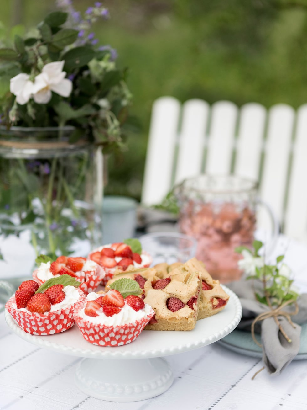 Det är uppdukat för somrigt fika i trädgården med hembakade kakor. Kakfat, Mio.