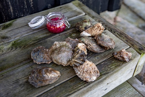 Medan musslorna tillreds i en stor utomhusgryta öppnas ostronen och slukas direkt på klipporna.
