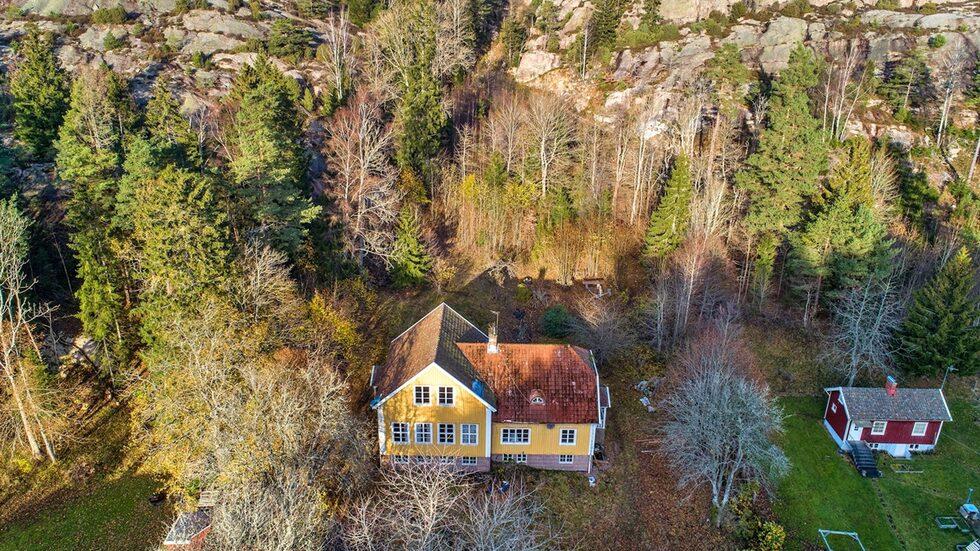 Huset ligger inbäddat bland berg och skog.