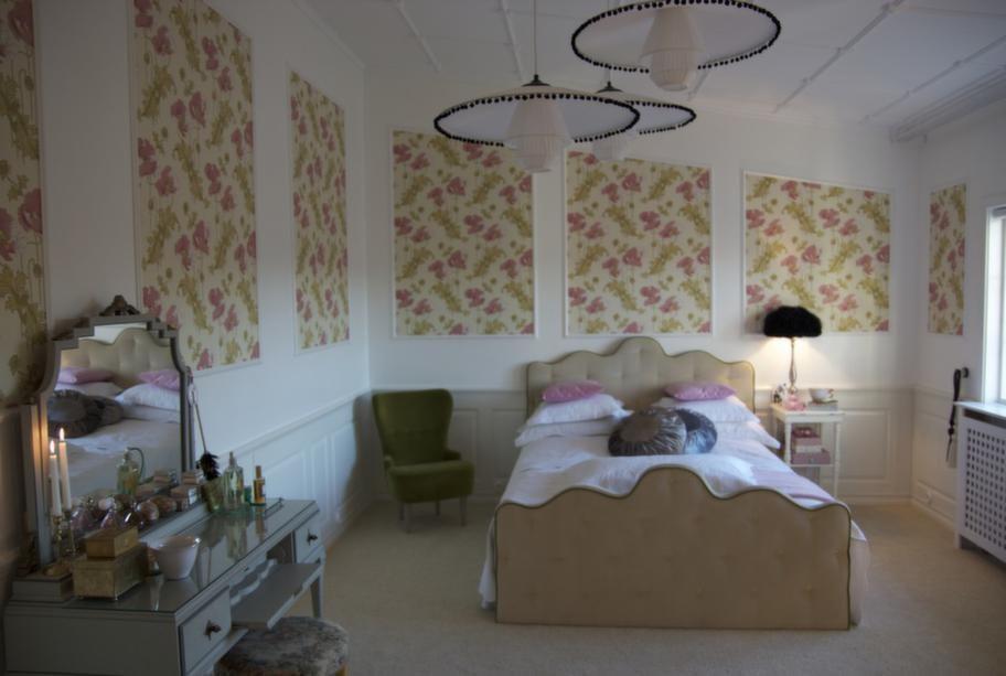 Efter. Mija har gjort nya sänggavlar i Mdf-material och fiberfill, som hon klätt i sammetstyg och fäst med möbelspik. På väggen stora ramar tapetserade med storblommig, romantisk tapet.