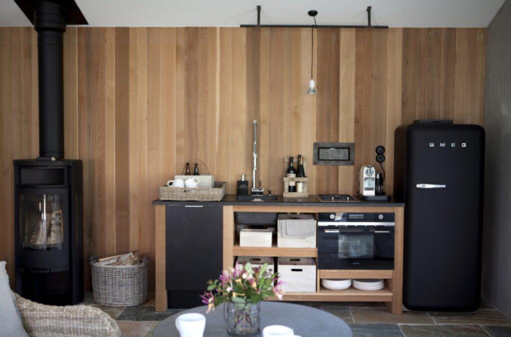 Det smakfulla köket går helt i mattsvart och cederträ. Modulerna som binder ihop köket är byggda efter Eva-Lenas önskningar. Upptill ligger en mattsvart matta som en golvläggare klätt in ovandelen med. Ugn, kyl och gashäll kommer från Smeg. Kaminen som värmer upp effektivt kommer från Contura.
