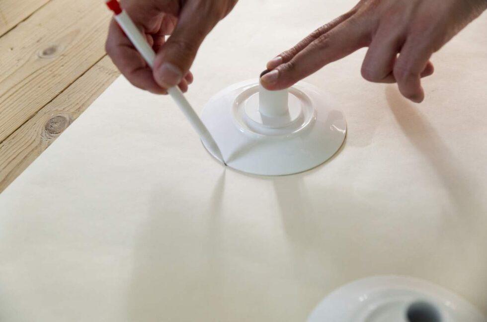 Bred ut ett stort papper på ett slätt underlag. Använd tallrikarna som mall och rita en cirkel. Klipp ut pappersmallarna.