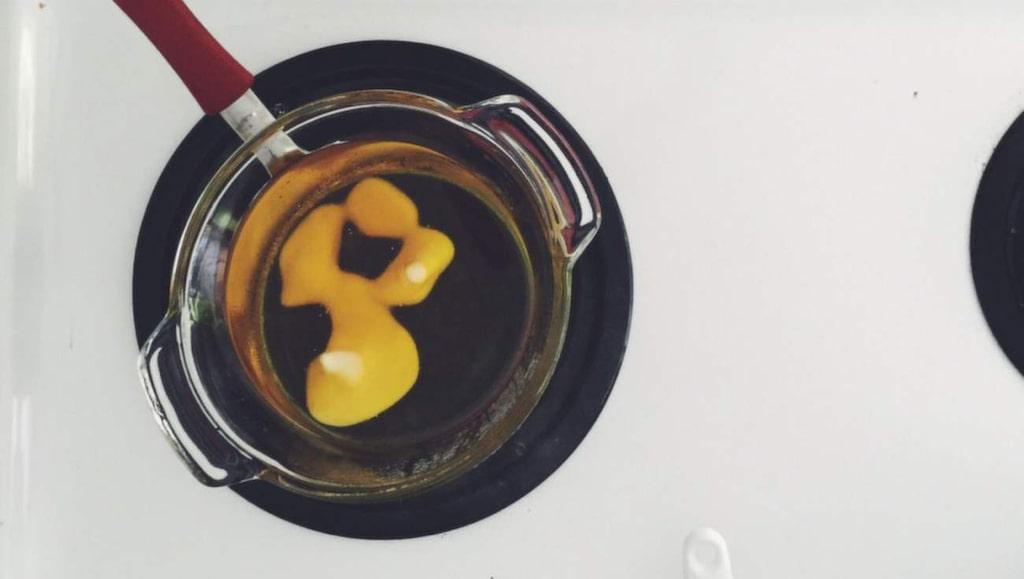 Bryt bivaxet och smält det i en glasskål som du sätter över en kastrull med sjudande vatten.