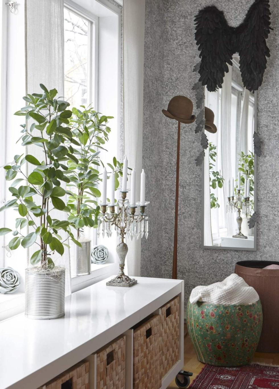 Förvaring från Ikea. Konservburkar som krukor, svarta vingar och en ärvd kandelaber skapar en trevlig hörna i sovrummet.