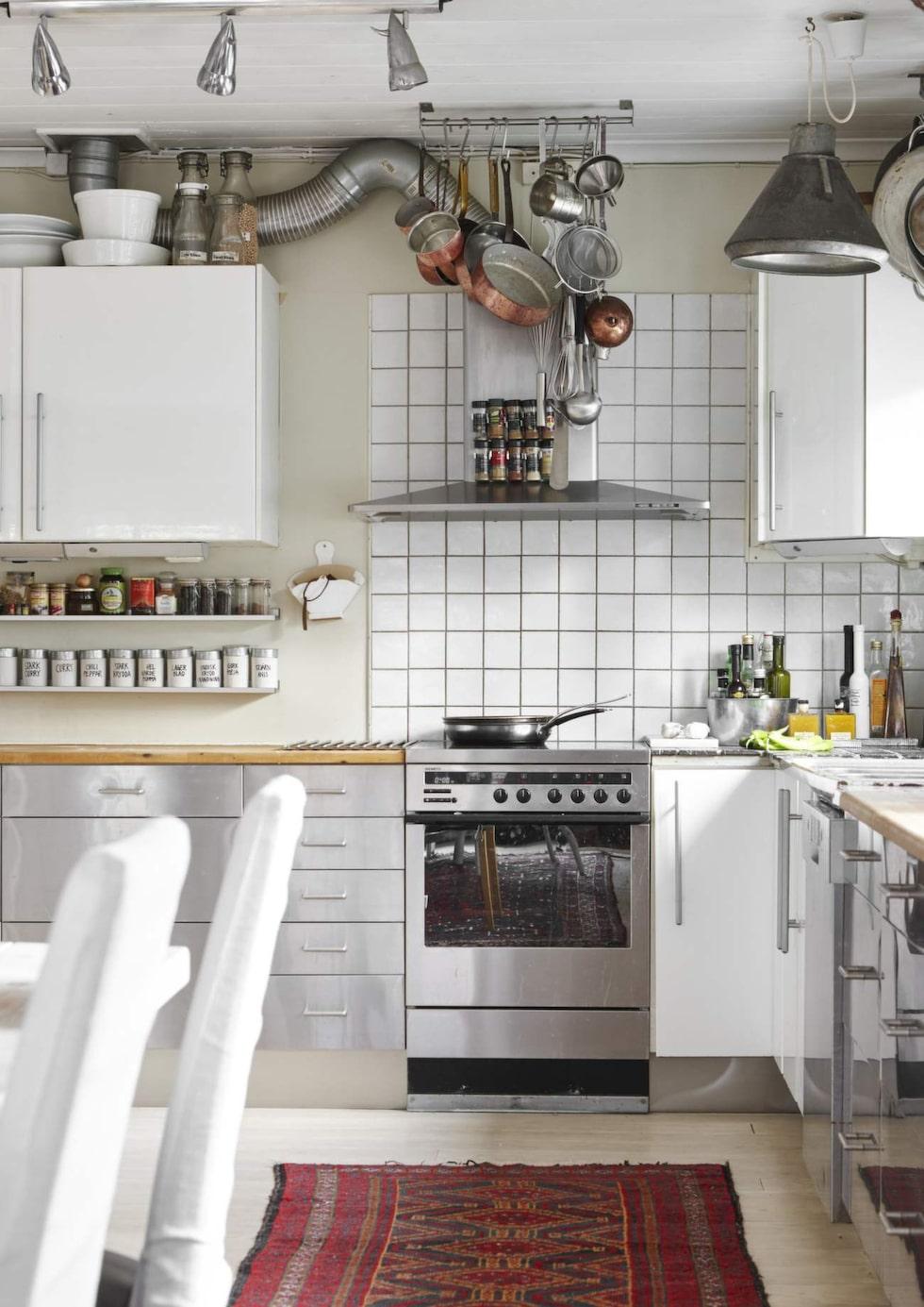 Kökets inredning är en mix av rostfritt och högblankt vitt tillsammans med en äkta matta, redskap i taket och rör som går utanpå väggen, precis så som Karin och René vill ha det.