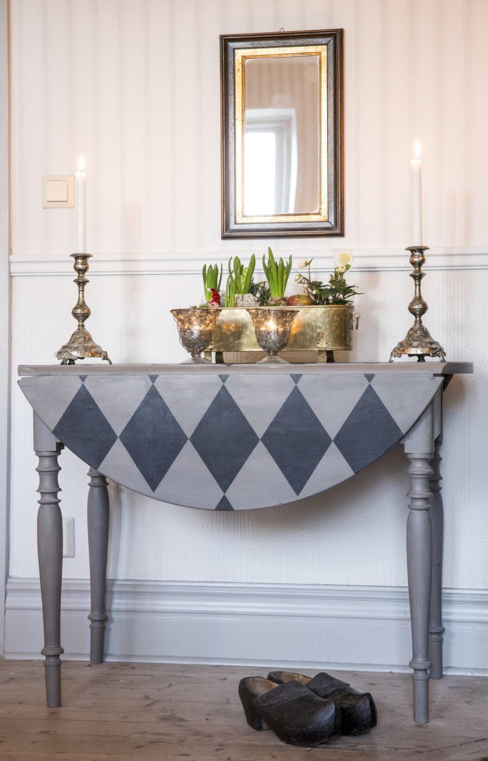Grå rutor. Det antika klaffbordet har Britt målat harlequinrutigt med kalkfärg från Annie Sloan. Ljusstakar och lyktor från Olsen & Jensen. I den antika mässingskrukan har Britt gjort ett jularrangemang av hyacinter och en julros.