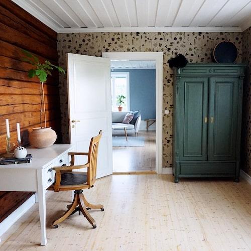 """Kammaren. """"Tapeten Botanica kändes som ett självklart val till timmerväggen här inne. Linneskåpet från min gammelfarmor målade jag om till den gröna kulören. Att ha inslag av naturen är något vi gärna vill ha, vi är ofta ute och plockar svamp eller kör skoter."""""""
