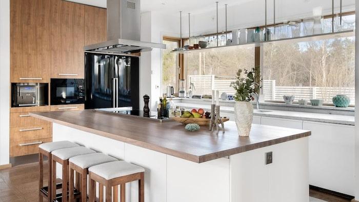 Köket är yrmligt med en stor köksö.