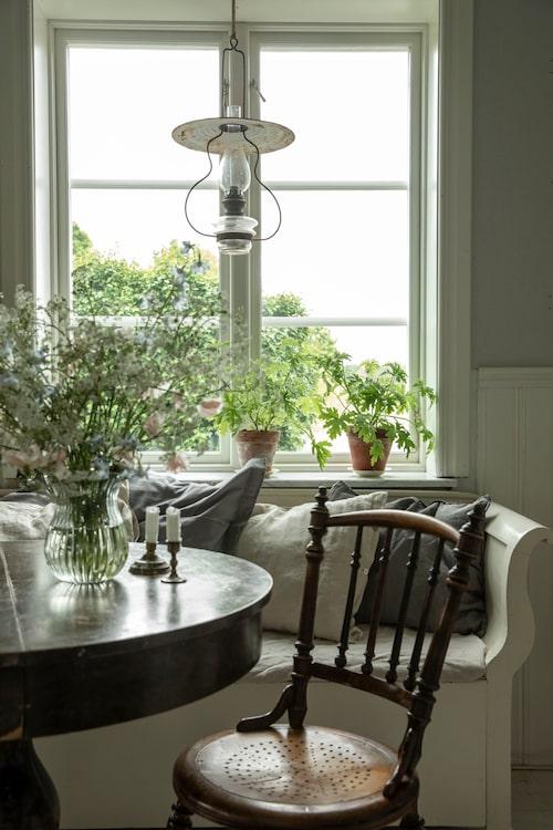 Matplats med barndomsminnen. Den fina vita kökssoffan som pryder matplatsen har Helena fått av en kollega. Matbordet är en gåva från Helenas mormors moster. Köksstolen, lampan och glasvasen på bordet är loppisfynd. Linnekuddar i kökssoffan, Jotex. Kökshandduk, Ikea.
