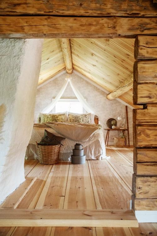 Emma-Lisas romantiska sovrum. Sängkappan kommer från Ellos och sänghimlen har Emma-Lisa gjort av två tunna gardiner från Ikea.  Textilierna på sängen kommer från Ikea och Mio. Golvet har sågats på en lokal såg, virket kommer från skogen i närheten.
