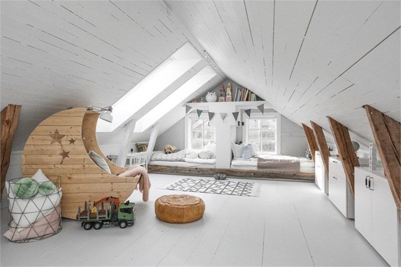 Från det första sovrummet tar man sig med trappa upp till vindsdelen. Rummet har massivt gråmålat trägolv och vitmålat trätak med synliga bjälkar. I taket sitter två stora takfönster från Velux med skugg- och mörkläggningsgardiner. I varsin del längst in i rummet finns två platsbyggda sängar. I sovrummet finns också ett mindre rum som är förberett för wc.
