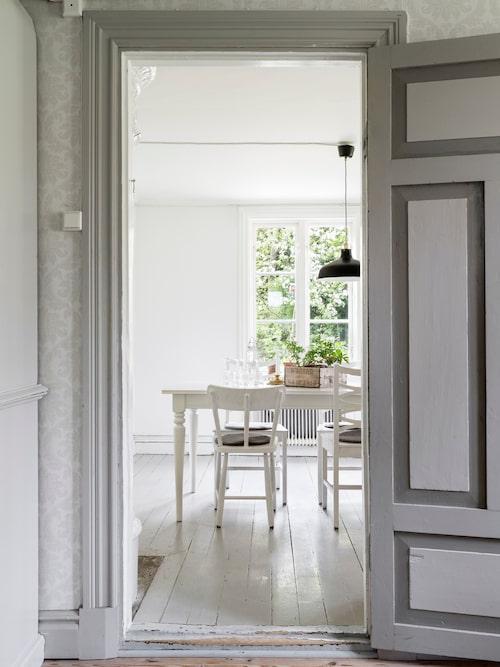 Britta och Martin har färgsatt den gamla dörren från vardagsrummet till matrummet i olika grå nyanser. Väggen är tapetserad med Borosan, Boråstapeter. Svart lampa från Ikea.