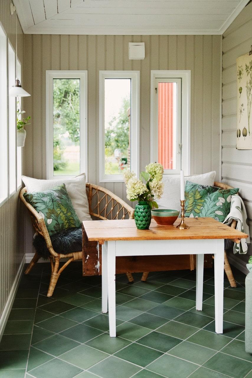Mysigt på verandan med korgstolar från Ikea och gröna toner på kuddarna.