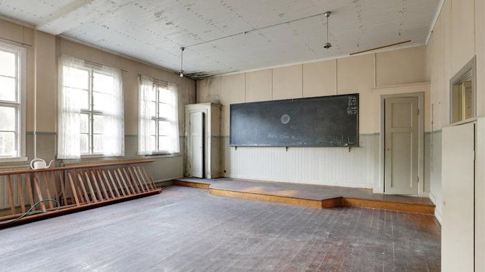 Den gamla skolsalen har fortfarande kvar sin upphöjda kateder med den svarta tavlan.