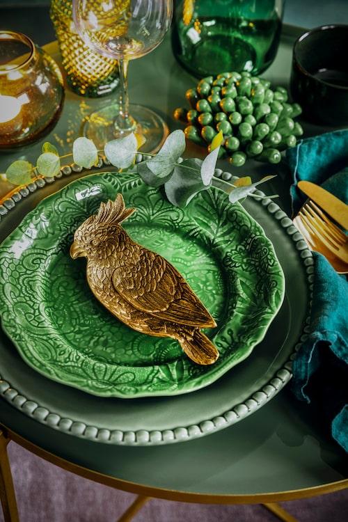 Grön tallrik med mönster, 200 kr, Pottery Jo. Grön assiett med mönster, 200 kr, Sthål. Papegoja i mässing, 469 kr, Welcome Home. Grön dekoration i porslin, 149 kr, Ellos Home.