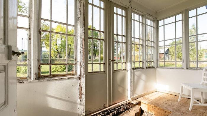 Inglasad veranda med vackra fönsterbågar och dubbeldörrar. Här har delar av golvet tagits upp för att ta bort organiskt material i grunden.