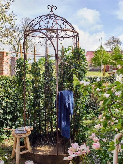 Karl Fredrik har planterat passionsblomma runt den charmiga duschen som ger både insynsskydd och blomsterfägring. Pall, tvål, badborste och handduk finns att köpa i butiken.