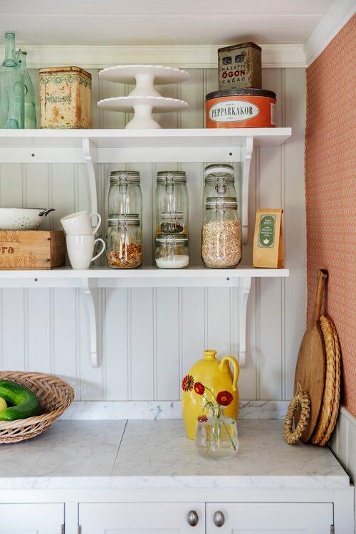 De öppna hyllorna i köket är fullt med gamla och nya prylar.