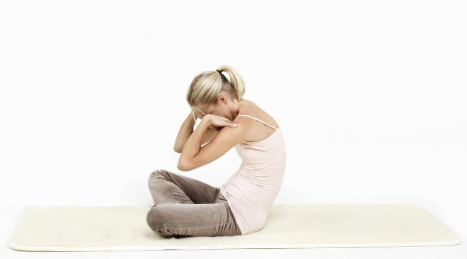 <strong>2. Långsam ryggflex</strong><br>Om du sitter på en stol, flytta en bit fram. Ta tag om knäskålarna, håll fast där. Tippa långsamt bäckenet så hela baken lägger sig ner på sitsen, krumma ryggen bakåt mot ryggstödet utan att sänka hakan, så långt armarna räcker.<br>Flexa sedan framåt så bröstkorgen trycker upp mot taket och svanken pressar framåt, utan att lyfta hakan mot taket. Andas in på vägen fram, andas ut på vägen bak. Tänk sat nam. Flexa tre till fem minuter. Avsluta med ryggen rak och ett rotlås. Vila en till två minuter.<br><br><strong>Obs: Se även nästa bild! </strong>