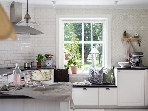 Kökets liggande kakel i halvförband förstärker den lantliga känslan liksom pärlsponten som återkommer på både väggar och köksö. Kök, Ikea. Tapet Edvin Willow Green, Sandberg.
