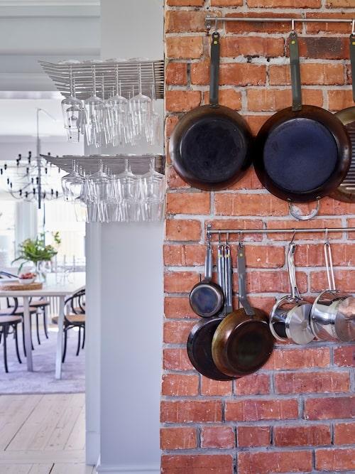 Uffe och Sofia har själva tillverkat stället för vinglasen som hänger på väggen. Stekpannorna hänger på ett ställ från Ikea.