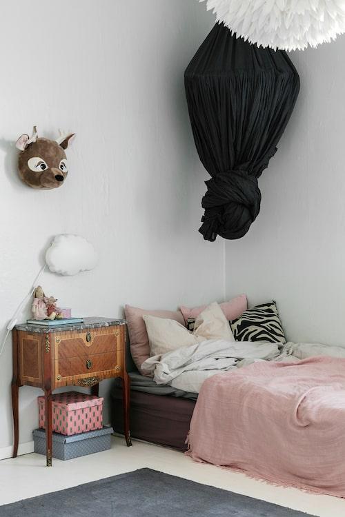"""I dottern Mollys rum har det svartvita fått en komplementfärg i mjukt rosa. Sängbord, Rusta. Vägglampa, Ikea. Rådjurshuvud H&H Home. Sängkläder, Hemtex. Askar Bungalow. Sänghimlen blir en mysig """"sovkoja"""" till kvällen. Sänghimmel, Ellos."""