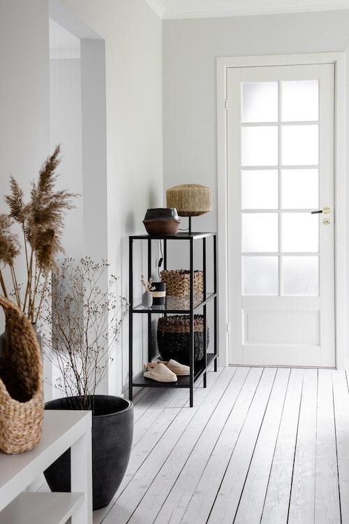 Hallen är ljus och inbjudande med vitlaserade golv. Glasdörren leder ner till källaren och ger ett extra ljusinsläpp.