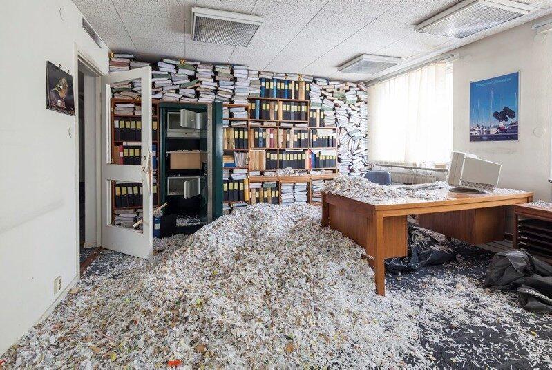 """Ett kontorsrum är helt fyllt med pappersstrimlor och bildar """"snöhögar"""", och bokhyllan är proppad med böcker, allt en del av killarnas installation i rivningsbyggnaden."""