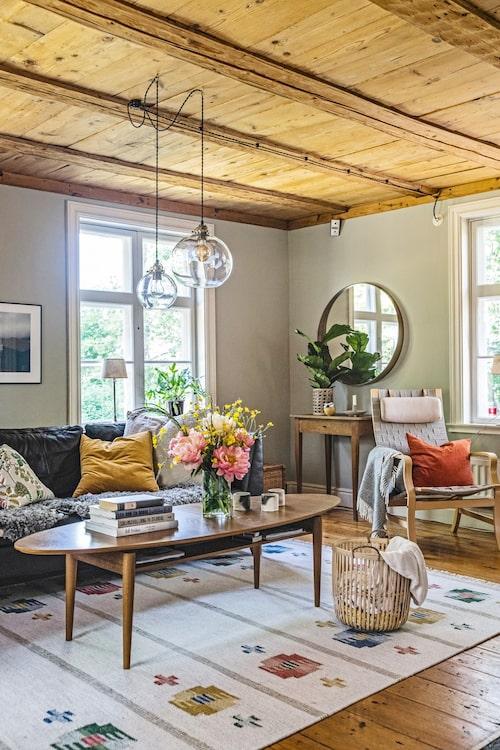 Vardagsrummet är husets bäst bevarade rum med vackra tiljor i taket och fönster i original med gammalt glas. Soffa och soffbord från Ikea. Mattan är en loppisfyndad födelsedagspresent från Hannas syster.