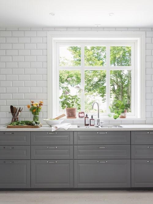För att få ett ljus och luftigt kök har Lina och Robin valt bort överskåp och i stället satt vitt kakel på väggen. Kök Metod med grå luckor Bodbyn och marmormönstrad kvartsbänkskiva, Ikea. Handtag, Superfront.