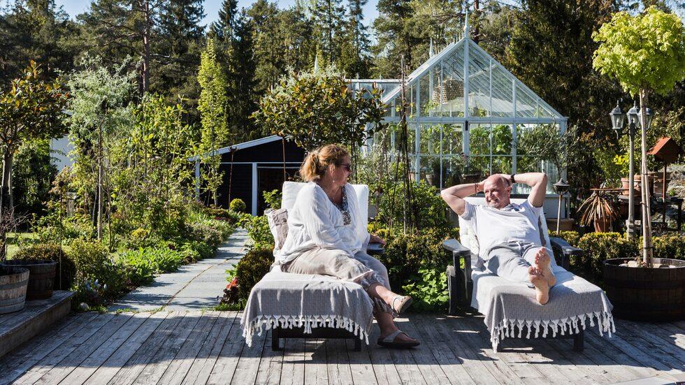 Med växthuset i bakgrunden sitter Maria och Pärlan på terrassen vid poolen och njuter av solens varma strålar. Växthus Spira, Bossons Living Room.
