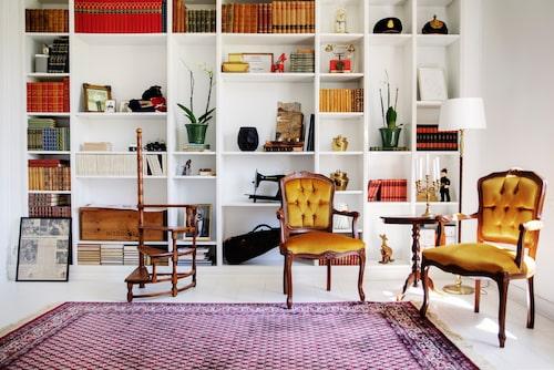 I bibliotekets bokhylla, som paret byggt av Ikeahyllor, samsas böcker med gamla saker och orkidéer. Stolar och bord, arvegods. Matta, Mattbolaget. Hyllor Billy, Ikea. Biblioteksstege, inropad på auktion.