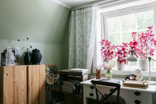 Hemmakontoret med det gamla skrivbordet har utsikt över trädgården och skogen utanför. I fönstret växer palettblad. Skåp Ivar, Ikea.