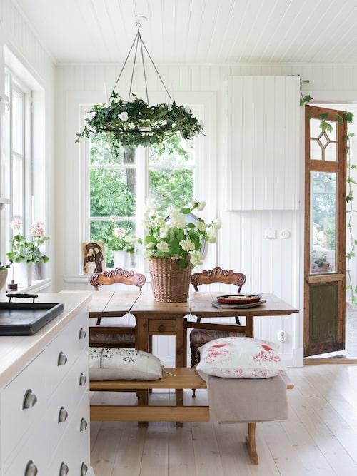 Det ljusa hemmet kombineras med möbler i trä, som skänker värme till rummen. Slagbordet och bänkarna i köket är antika. Takkronan över bordet smyckas efter årstid, som här i en sommarskrud av murgröna. På bordet står ett fång med hortensia, som Jennie plockat i trädgården.