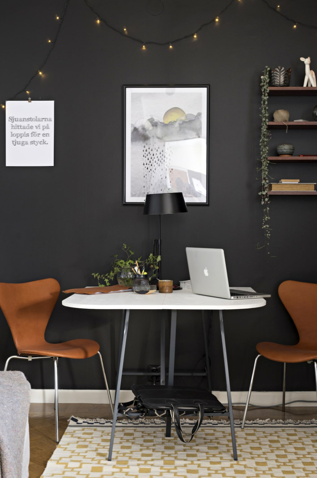 Den mörka fondväggen framhäver möblerna. Bordet är byggt av hyllplan i furu från Biltema och benbockar Lerberg från Ikea. Sjuanstolarna är Blocket-fynd som renoverats av Anna och som klätts med skinn från Tärnsjö garveri. Matta Alvine Ruta från Ikea.