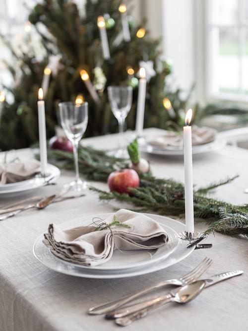 Julbordet är dukat med granis, röda juläpplen och vackert linne.