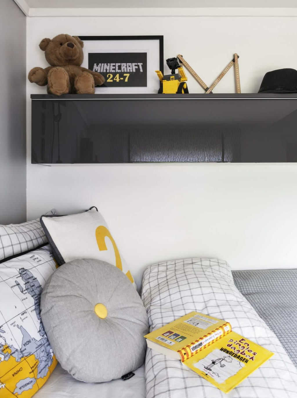 Snygga kuddar med gula stänk blir en fin kontrast till basfärgerna grått, vitt och svart i rummet. Sängkläder, Kid. Överkast, Skeidar. Kuddarna med kartor och siffror, Kremmerhuset.