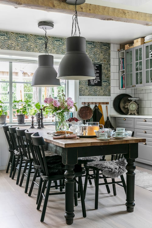 Här finns plats för ett stort matbord för tio personer. Ovanför bröstpanelen är väggen klädd med tapeten Wandle från William Morris. Kök Bodbyn, Ikea. Bord, Olsson & Jensen. Matstolar och taklampor, Hektar, Ikea.