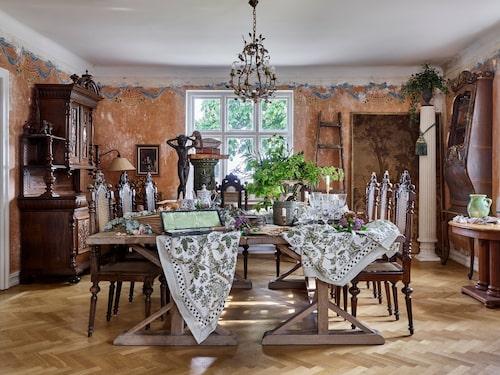 Den vackra matsalen har kvar sina fantastiska väggmålningar från när huset byggdes. Här inne dukar paret gärna upp till stora middagar. De pampiga träborden som nu är placerade i en kvadrat kan lätt ändras om till långbord.