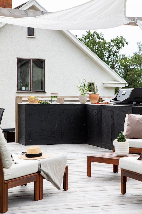 Det svarta L-formade uteköket har nedsänkt grill och diskho.