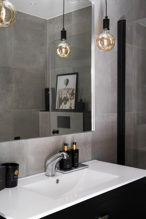 Den grå färgskalan återkommer i det andra badrummet. Kommod och handfat från Bygghemma.