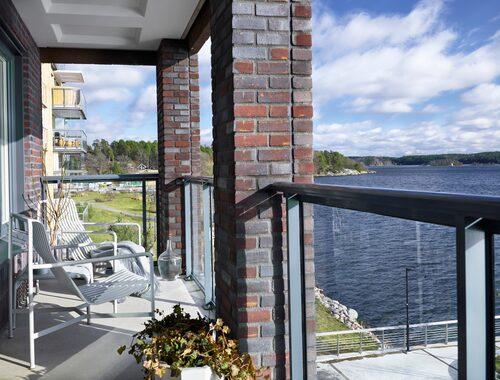 """Balkong med utsikt över vattnet. """"Det är en av Björns och mina favoritplatser i hemmet. Balkongen rymmer också ett litet matbord där vi äter frukost om vädret tillåter."""""""