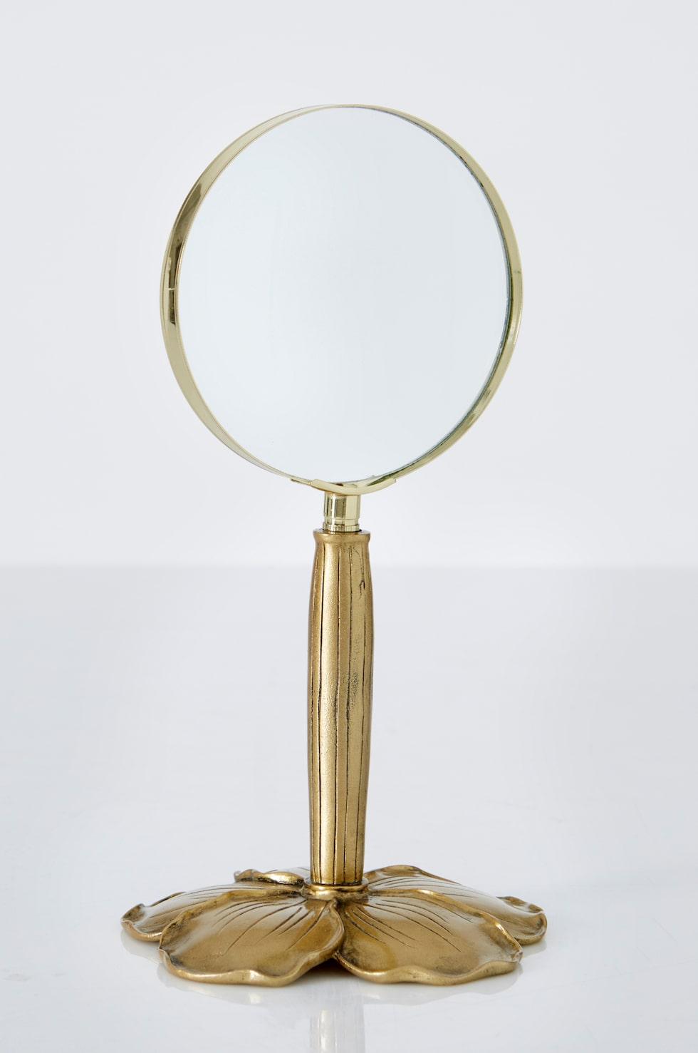 """""""Velona"""" heter förstoringsglaset/spegeln på fot av fint arbetad mässingfärgad metall i form av en blomma. Höjd 23 cm. Glasets diameter ca 10 cm. Pris: 399 kronor."""