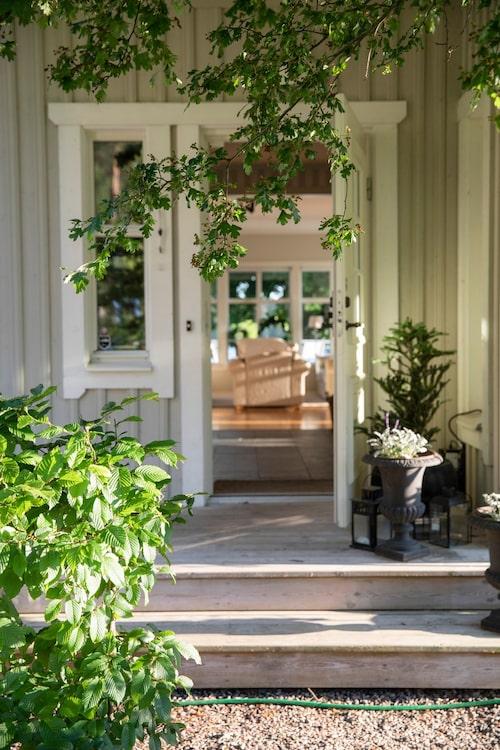 Den vackra entrén ger direktkontakt med det nybyggda husets vardagsrum och matrum. Kruka från Carins butik. Fasaden är målad i kulören Bestå Sandsten 151, Alcro.