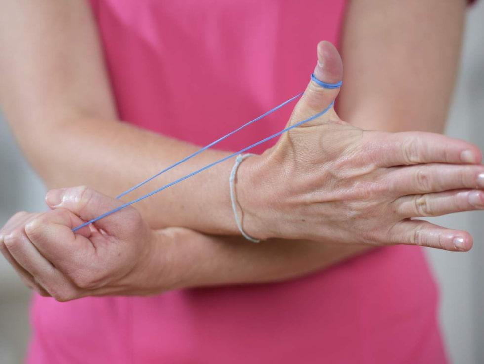 Artros-övning 1: Tummens framsidaLinda ett gummiband runt ena tummen. Håll i andra änden och sträck ut gummibandet. För tummen mot handflatan och för sedan sakta tillbaka. För mer motstånd, sträck gummibandet mer. Upprepa med andra tummen.
