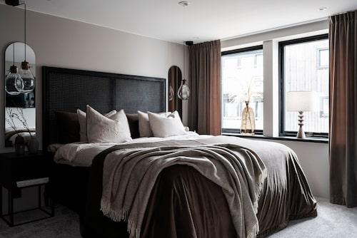 Sovrummet går i dova jordnära färger. De båda speglarna reflekterar ljuset från fönstren och ger en lyxig inramning till sängen. En heltäckningsmatta mjukar upp och fortsätter in i parets walk-in closet. Sänggavel, Ellos Home. Speglar, Åhléns. Pendellampor, H&M Home.