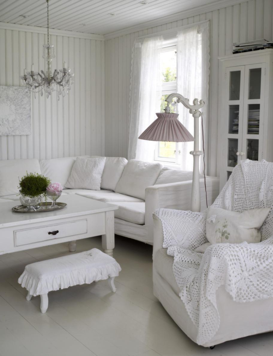Vardagsrum. I den rymliga soffan finns plats för många. Mjuka textilier i vita nyanser får sätta prägel på rummet.
