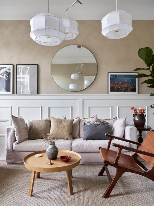 Vardagsrummet är favoritrummet och andas sekelskifte med vackra paneler, stuckaturer, ljusa trägolv och kalkmålade väggar som fond åt möblemanget i skandinavisk stil.