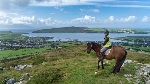 På hästryggen med vidsträckt utsikt över staden Dingle och havet.