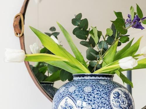 Den blå vasen är fyndad på loppis. Spegeln från Ikea har klätts med två läderbälten.